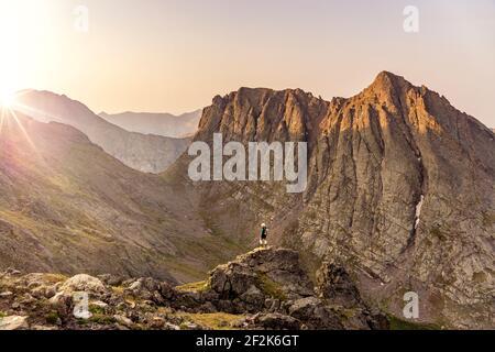 Mujer mirando a la vista mientras está de pie en la cima de la montaña contra el cielo despejado durante la puesta de sol