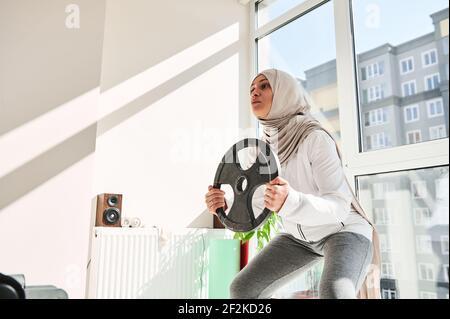 Mujer musulmana árabe con el tocado usando hijab haciendo escuadrones ponderados con un disco de metal en sus manos - concepto de entrenamiento en casa. Foto de stock