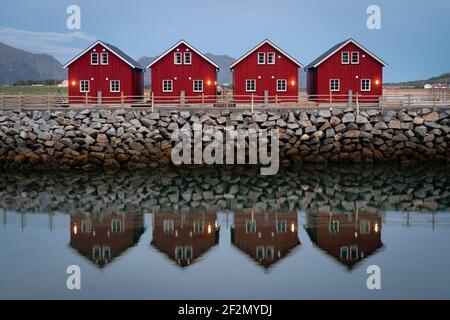 cabañas clásicas de pesca rojas con perfecta simetría sentadas a lo largo de un embarcadero de piedra con un reflejo ligeramente borroso. Casas clásicas rojas del norte de noruega