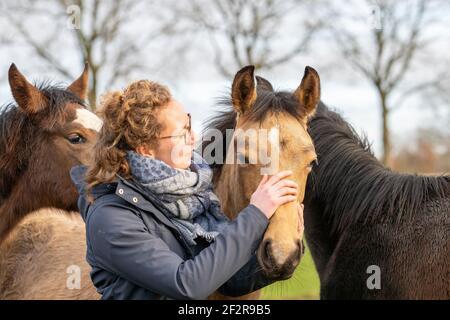 Mujer joven en un abrigo de cera con sus 1 años de edad en el pasto. Ella se cudda con ellos para socializarlos. Tres cabezas de caballo
