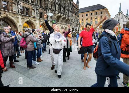 """Munich, Baviera, Alemania. 14th de marzo de 2021. Los negadores y antienmascaradores de Corona participan en un baile Polonaise sin distanciarse y la mayoría sin máscaras en Marienplatz de Múnich. A pesar del aumento de los números de Corona de la variante británica, la policía mantuvo un enfoque relajado. Con ocasión de Alemania entrando en un período de medidas anti-Corona hace aproximadamente un año, los negadores y antienmascaradores de Corona dirigidos por Querdenken€℠â Markus Haintz se reunieron en Munich€"""" â Marienplatz y luego en MaxMonument en un esfuerzo por protestar contra el Landtag bávaro y promover su iniciativa para disolverlo"""