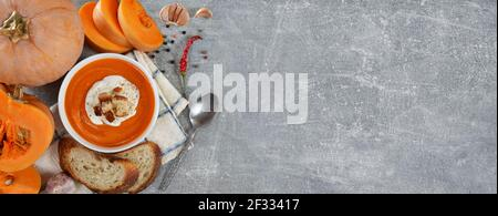 Sopa recién hecha de crema de calabaza picante con crema agria y croutones en un tazón blanco junto a calabaza fresca, rebanadas de pan y especias en un backg gris