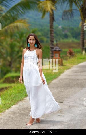 Bonita mujer bronceada con vestido blanco posando en el camino. En el fondo hay palmeras y otra vegetación tropical.