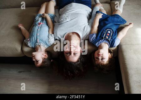una joven madre y dos hijas están mintiendo el sofá boca abajo