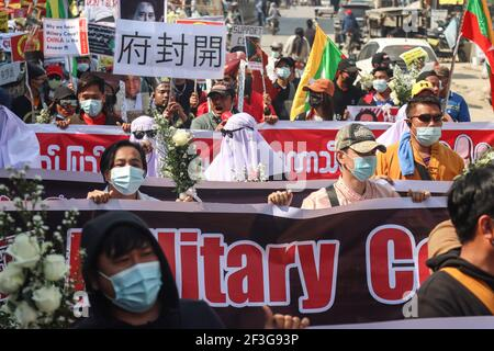 Muse, Estado de Shan del Norte, Myanmar. 13th de febrero de 2021. Los manifestantes contra el golpe militar tienen varias banderas grandes durante una manifestación pacífica contra el golpe militar.UNA muchedumbre masiva tomó las calles de Muse (ciudad fronteriza birmana con China) para protestar contra el golpe militar y exigió la liberación de Aung San Suu Kyi. Los militares de Myanmar detuvieron a la Consejera de Estado de Myanmar Aung San Suu Kyi el 01 de febrero de 2021 y declararon un estado de emergencia mientras se apoderaban del poder en el país durante un año después de perder las elecciones contra la Liga Nacional para la Democracia (imagen de crédito: © Mine SMI