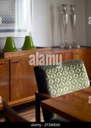 Silla tapizada en frente de la unidad de almacenamiento de madera en el apartamento, Brasil