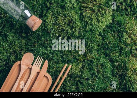 Botella de vidrio, cubertería de bambú ecológica, embalaje, recipientes para comida para llevar para picnic o almuerzo sobre fondo de musgo verde. Vista superior. Espacio de copia
