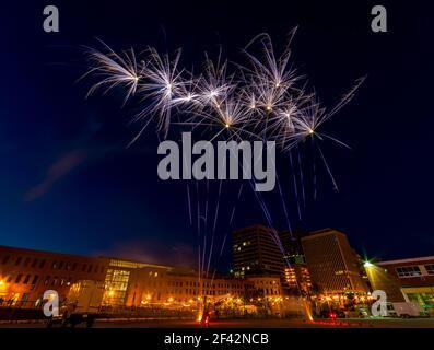 Fuegos artificiales. Gran angular que muestra el lanzamiento, así como las floraciones. Edificios y luces de calle en el fondo. El foco está en los fuegos artificiales.