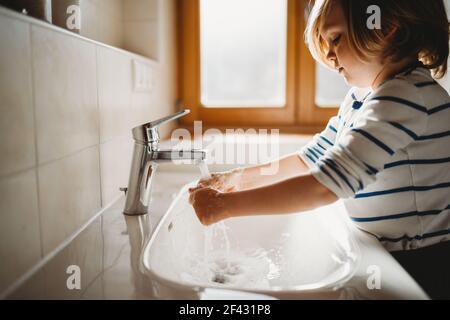 Vista lateral de niños en edad preescolar que se lavan las manos con jabón