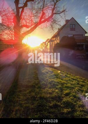 Tarde en una pequeña ciudad alemana. Una calle a lo largo de algunas casas conduce a la puesta de sol. Los rayos del sol golpearon la cámara exactamente. El pasto y el pasto