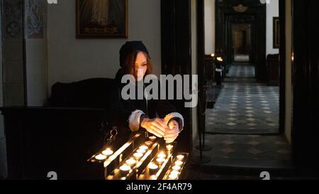Una joven mujer caucásica sosteniendo sus manos sobre velas encendidas de té redondas en la iglesia católica interior.in Cracovia, Polonia. Foto de stock