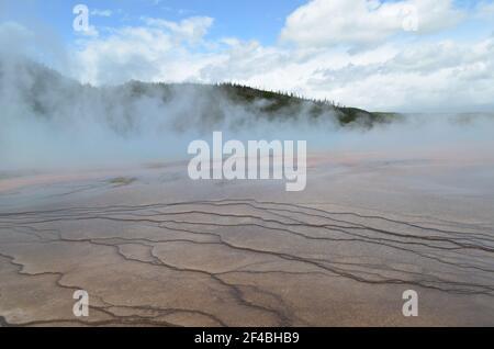 Finales de primavera en el Parque Nacional Yellowstone: Los colores de la Gran Primavera Prismática vista a través del vapor en el Grupo Excelsior de Midway Geyser Basin