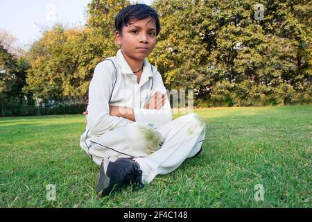 un niño sentado en el suelo durante un cricket