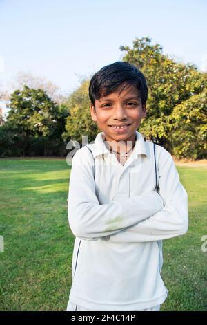 Un chico con uniforme de críquet de pie