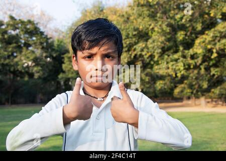 Un chico en uniforme de cricket y señalando