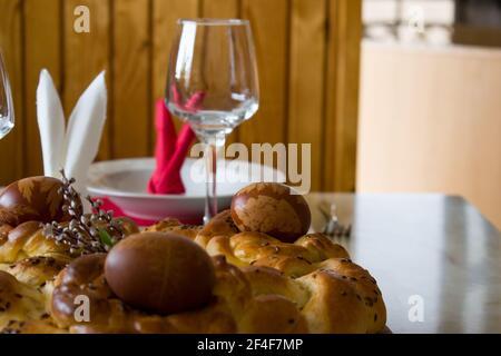 Tradicional pan trenzado casero y huevos de Pascua teñidos con pieles de cebolla. De cerca decoración de mesa de Pascua