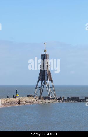 Cuxhaven, Alemania - 14 de marzo de 2021: Excursionistas de un día visitando la baliza de Kugelbake, punto de referencia de la ciudad en el estuario del río Elba.