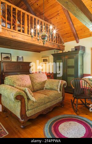 Sofá tapizado amarillo-marrón, mecedora de madera antigua, armario de madera de pino verde y un gran piano en el gabinete Howard en la habitación familiar