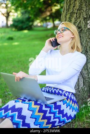 Niña sentada hierba con cuaderno. Mujer con ordenador portátil en el parque orden artículo en el teléfono. Chica se aprovecha de las compras en línea. Ahorre tiempo con las compras