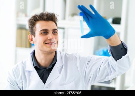 Sonriente hombre científico examinando líquido en el tubo de ensayo