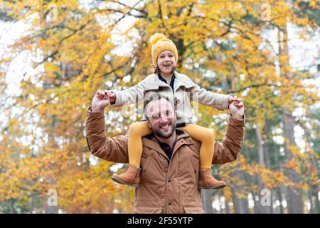 Padre juguetón llevando a una hija sonriente mientras estaba de pie en el bosque