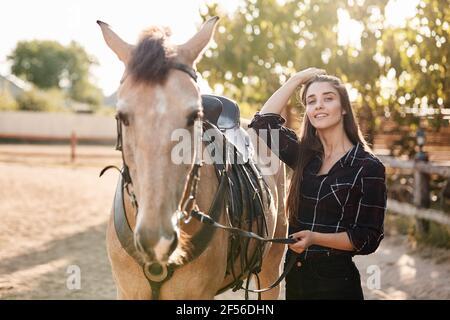 Encantadora equitación, jinete femenino de pie con su lindo caballo marrón favorito, sosteniendo el ala, poner silla, wanna tomar paseo por la mañana, pasar el tiempo