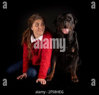 purebred rottweiler y mujer delante de fondo negro