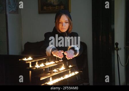 Una joven mujer caucásica sosteniendo sus manos sobre velas encendidas de luz de té de forma redonda, cara concentrada iluminada por la luz. Foto de stock