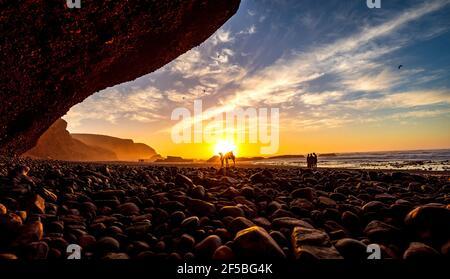 Cielo de puesta de sol sobre fenómeno natural puente arco de piedra de la playa de Legzira con camello dromedario frente al bajo sol, océano Atlántico, Marruecos