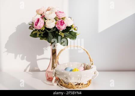 Huevos coloridos de Pascua en buket sobre mesa de madera blanca. Ramo de flores de rosas en el fondo. Felices Pascuas. Estado de ánimo de primavera.