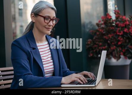 Mujer de negocios madura usando computadora portátil, trabajando en línea. Retrato de un copywriter asiático de mediana edad con gafas elegantes escribiendo en el teclado