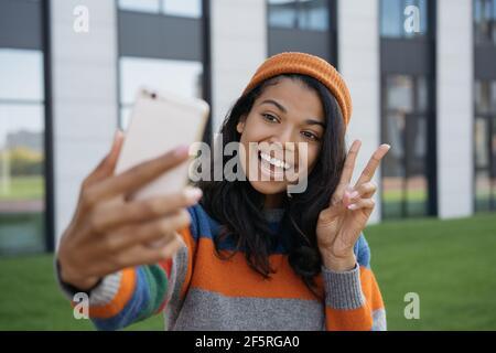 Joven blogger emocional influencer utilizando el teléfono móvil, streaming de vídeo en línea. Sonriente mujer afroamericana tomando selfie, mostrando signo de victoria