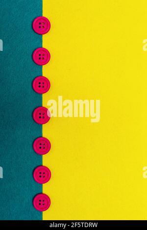 Vista superior de botones de colores que representan las sombrillas entre la costa arenosa y agua de mar verde