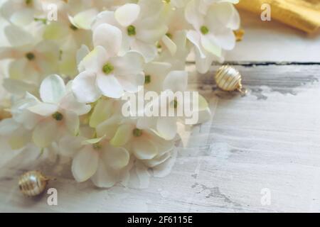 vista de cerca de la floreciente hidrangea blanca con cuentas doradas sobre fondo de madera