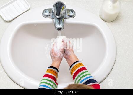 Un niño pequeño se lava las manos con jabón en el baño
