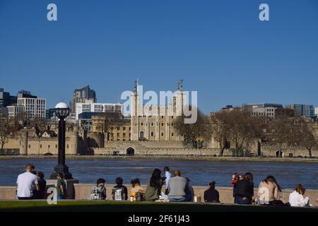 Londres, Reino Unido. 29th de marzo de 2021. La gente disfruta del sol en Potters Fields Park con una vista de la Torre de Londres como las reglas de cierre se relajan en Inglaterra. Crédito: Vuk Valcic/Alamy Live News