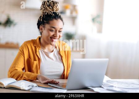 Inteligente atractivo feliz carrera mixta chica negra con dreadlocks, en ropa informal, estudiar a distancia, ver información en línea, hablar en conferencia con el profesor o colegas, sonriendo