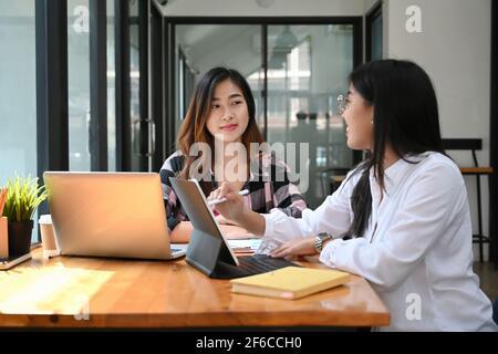 Dos jóvenes diseñadores creativos discutiendo ideas y trabajando con dispositivos modernos en la oficina.