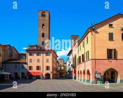 Vista de la plaza de la ciudad adoquinada entre antiguas casas coloridas y torres medievales bajo el cielo azul en Alba, Piamonte, Norte de Italia.