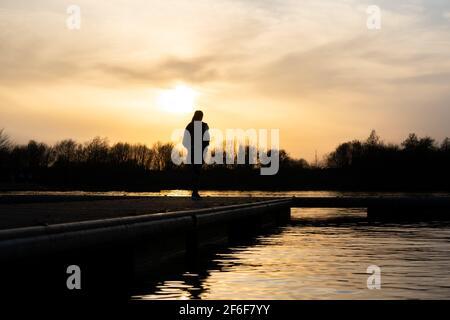 Mujer de pie sola al atardecer en el extremo del muelle del lago, el muelle pensativo y tranquilo río abajo. Sol de oro verano sin luz que se refleja en el agua solo