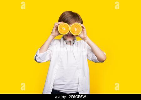 El niño caucásico está cubriendo su ojo con limones en rodajas sonriendo en una pared de estudio amarilla