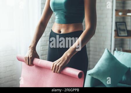 Ajuste la mujer caucásica lleva ropa deportiva mientras reúne el yoga estera