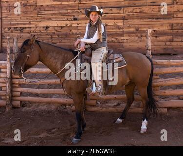 Una joven y atractiva vaquera wrangler posa sobre su caballo en un rancho cerca de Moab, Utah. Ella usa brochones de cuero para protegerla del cepillo espinoso w