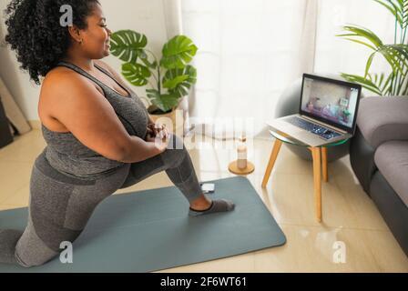 Una joven africana que hace pilates clase de fitness virtual con portátil En casa - Deporte bienestar personas concepto de estilo de vida