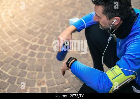 Hombre haciendo estiramientos y escuchando música después del entrenamiento. Hombre descansando durante el jogging de la ciudad. Corredor con teléfono móvil conectado a una grabación de Smart Watch