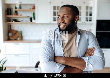 Retrato de joven alegre hombre afroamericano con barba con auriculares de pie en la sala de estar, con ropa elegante, mirando hacia un lado, los brazos cruzados frente a él, sonriendo