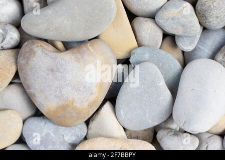 Fondo y textura de guijarros con un guijarro en forma de corazón ellos
