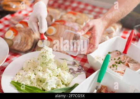 Trabajar en una carnicería - un asistente de tienda con queso rizado (solo se pueden ver las manos)