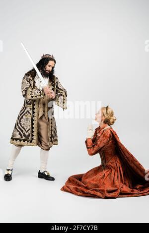 toda la longitud del cruel rey hispano en la celebración de la ropa medieval espada cerca de la reina asustada en la corona sentada con las manos de oración en blanco Foto de stock