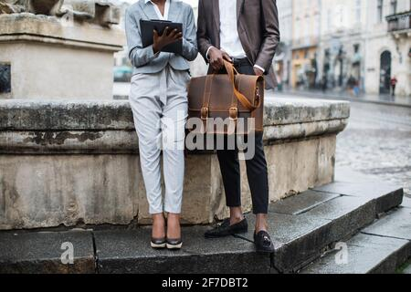 Primer plano de una mujer afro americana con portapapeles y un joven con maletín sentado al aire libre. Dos colegas de negocios resolviendo problemas de trabajo urgentes en la calle.